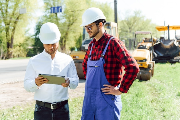 Engenharia civil, construção de estradas. o conceito de construção de uma nova estrada de asfalto. reparação de estradas. trabalhador de serviço rodoviário perto da pista.