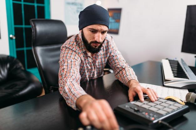 Engenharia de áudio, homem trabalha com teclado musical