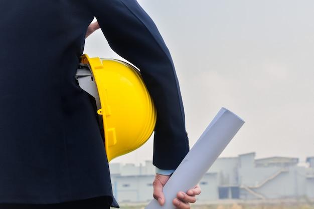 Engenharia de construção segurando a planta do capacete amarelo no fundo da construção