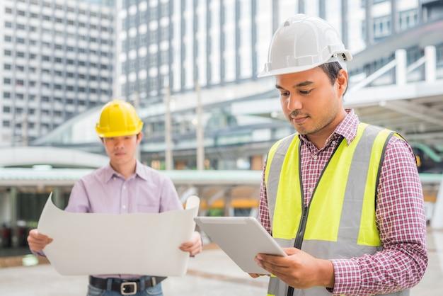 Engenharia de dois asiáticos que verifica o plano no canteiro de obras.