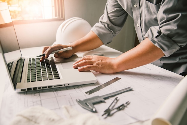 Engenharia está trabalhando no projeto, construção na mesa de trabalho com equipamentos de trabalho.