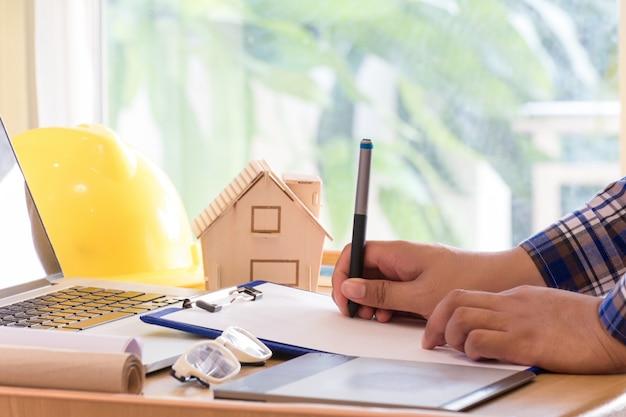Engenharia que trabalha com o escritório do caderno, da tabuleta e do telefone celular no domicílio.