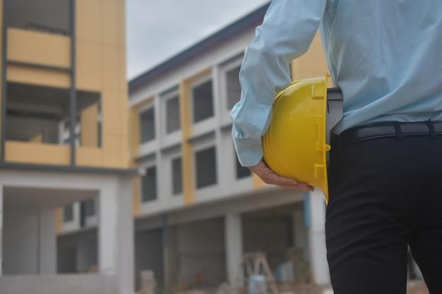 Engenharia, segurando o capacete amarelo no canteiro de obras
