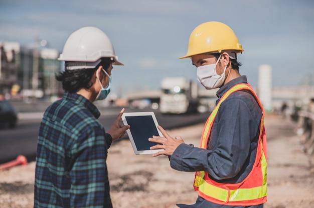 Engenharia, segurando o trabalho do tablet na construção de estradas