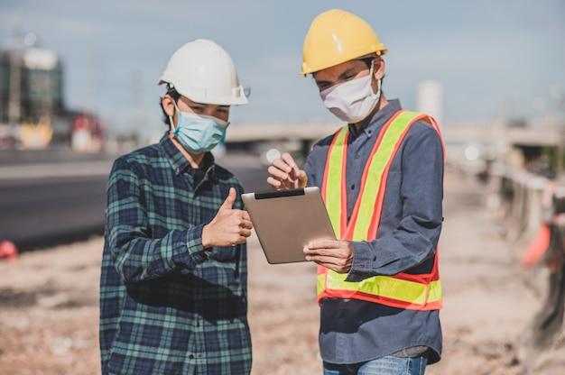 Engenharia, segurando o trabalho do tablet no foco da construção de estradas no tablet