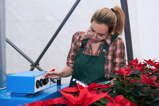 Engenheira agrícola verifica o funcionamento do equipamento de aquecimento em um viveiro de plantas com efeito de estufa