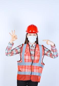 Engenheira civil com capacete vermelho e máscara de segurança, mostrando sinal de sucesso