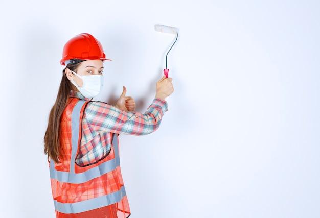 Engenheira civil com máscara de segurança e capacete vermelho, segurando um rolo aparador e pintando a parede com a cor azul