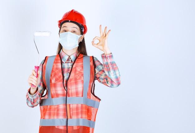 Engenheira civil com máscara de segurança e capacete vermelho segurando um rolo aparador para pintar e mostrando uma placa de prazer