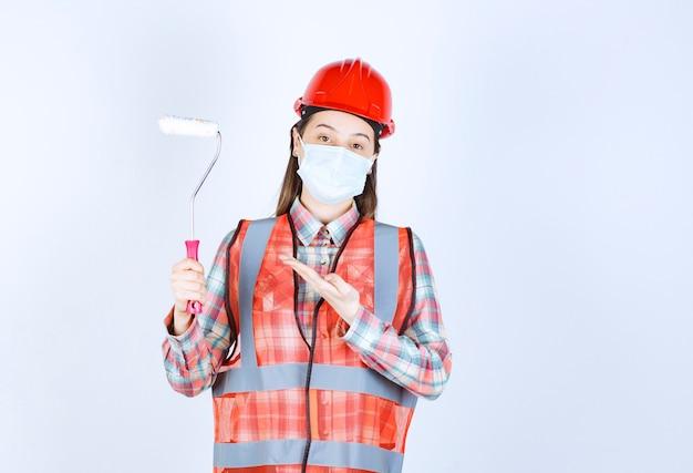 Engenheira civil com máscara de segurança e capacete vermelho segurando um rolo aparador para pintar
