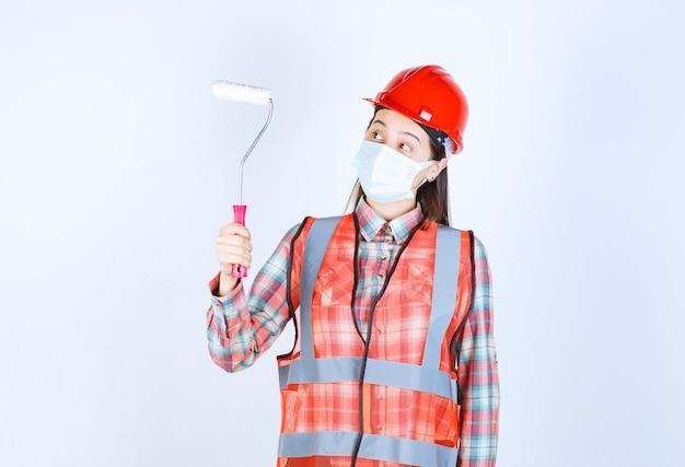 Engenheira civil feminina na máscara de segurança e capacete vermelho segurando um rolo aparador para pintura e parece confusa.