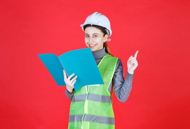Engenheira com capacete branco, segurando um arquivo de projeto azul, lendo e pensando.