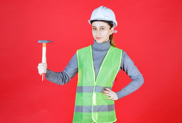 Engenheira com capacete branco segurando um machado de madeira.