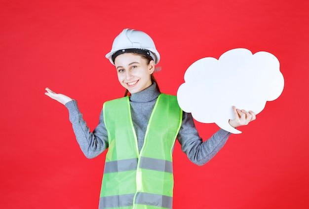 Engenheira com capacete branco segurando uma placa de informações de forma de nuvem e parece confusa e inexperiente.