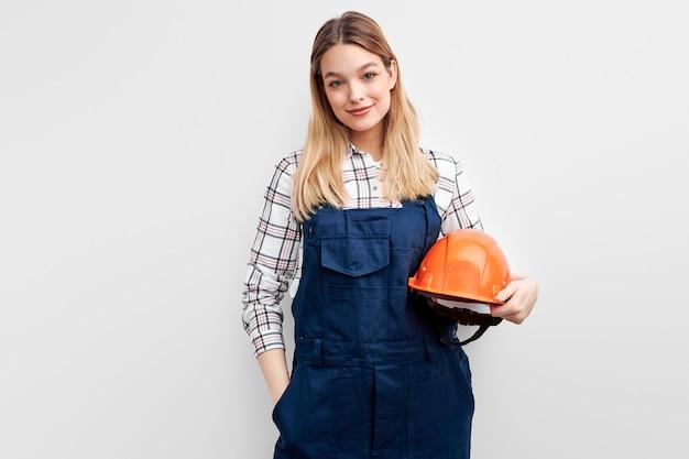 Engenheira com capacete laranja em pé com expressão positiva, vestida com uniforme de construtor e olhando para a câmera sobre fundo branco