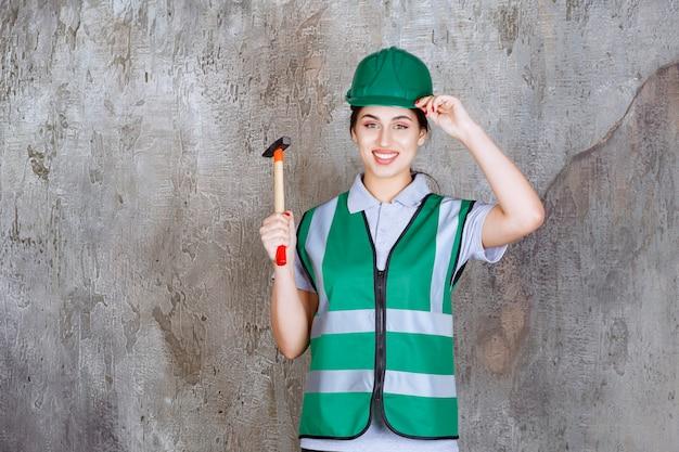 Engenheira com capacete verde segurando um machado com cabo de madeira para uma obra de reparo