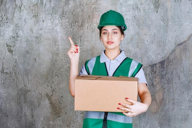 Engenheira com capacete verde segurando uma caixa de papelão e apontando para alguém ao redor