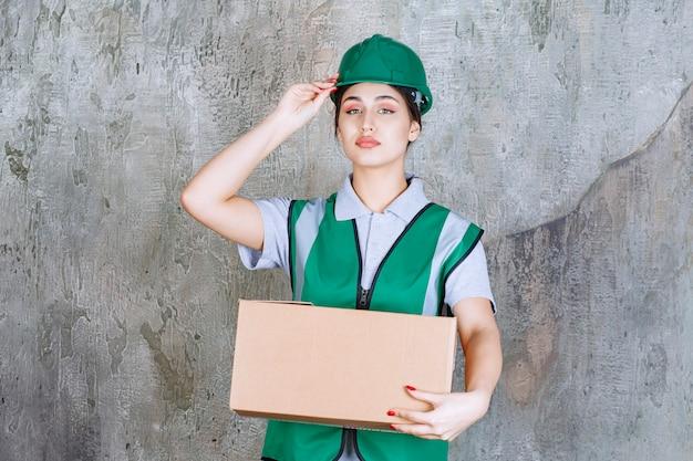 Engenheira com capacete verde segurando uma caixa de papelão