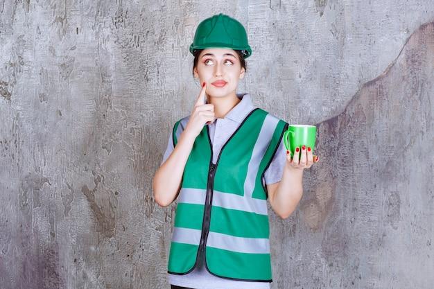 Engenheira com capacete verde segurando uma caneca de café verde e pensando