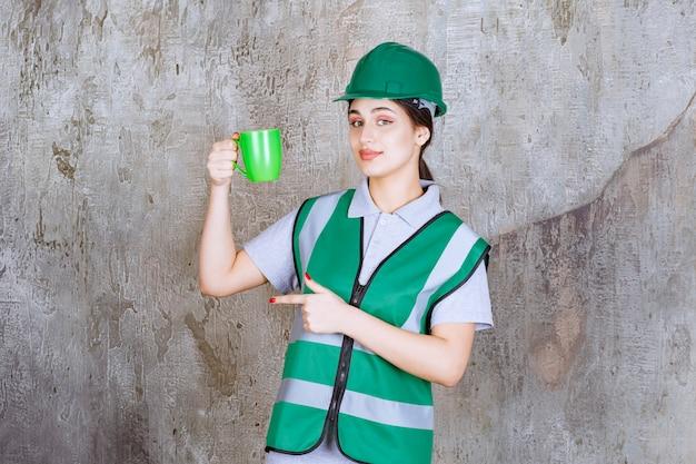 Engenheira com capacete verde segurando uma caneca de café verde