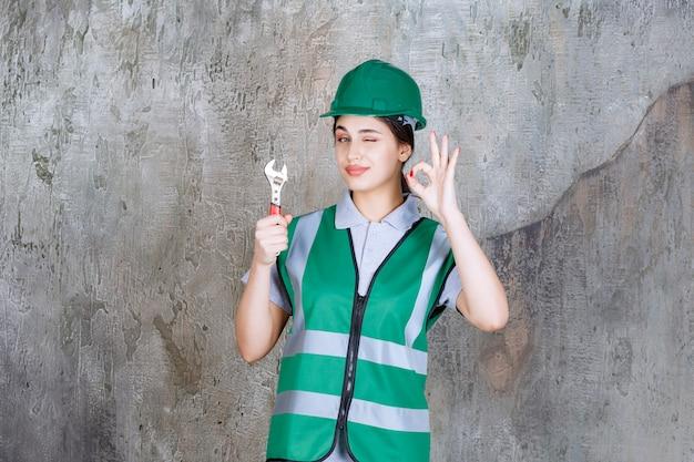 Engenheira com capacete verde segurando uma chave metálica para um trabalho de reparo e mostrando sinal de prazer