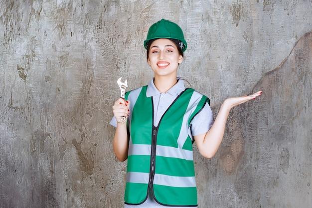 Engenheira com capacete verde segurando uma chave metálica para uma obra de reparo