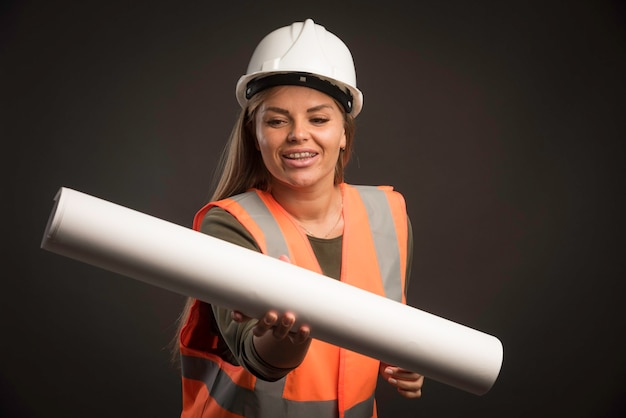 Engenheira com um capacete branco segurando o plano do projeto e parece confiante.