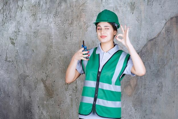 Engenheira com um capacete verde segurando um alicate para uma obra de reparo e mostrando um sinal positivo com a mão
