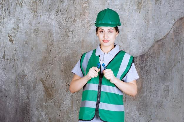 Engenheira com um capacete verde segurando um alicate para uma obra de reparo
