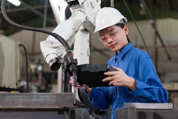 Engenheira de automação feminino usa um uniforme azul com controle de inspeção de segurança do capacete uma máquina de solda de braço robô com um sistema remoto em uma fábrica industrial. conceito de inteligência artificial.