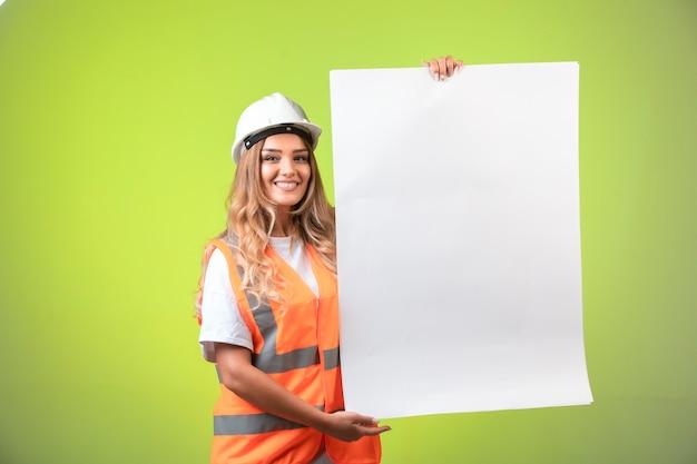 Engenheira de capacete branco e equipamento mostrando o plano de construção e as normas.