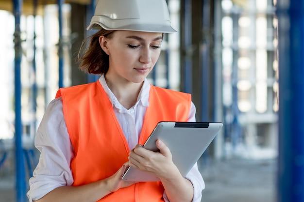 Engenheira de construção. arquiteto com um computador tablet em uma construção. jovem mulher olhando, construindo local de construção no fundo. conceito de construção.