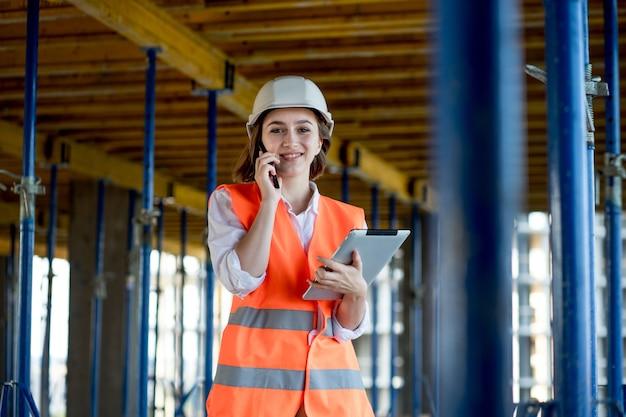 Engenheira de construção. arquiteto com um computador tablet em uma construção. jovem mulher olhando, construindo local de construção no fundo. conceito de construção