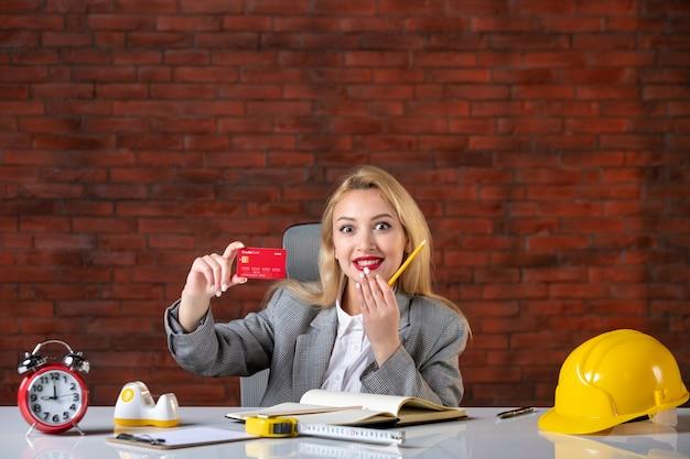 Engenheira de frente, sentada atrás de seu local de trabalho