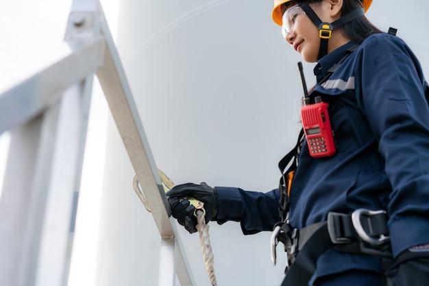 Engenheira de inspeção usando arnês de segurança e cordão de segurança