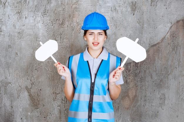 Engenheira de uniforme azul e capacete segurando duas placas de informação em branco com as duas mãos e parece insatisfeita.