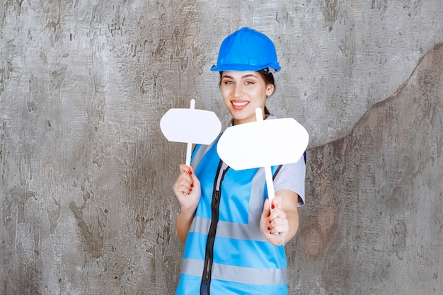 Engenheira de uniforme azul e capacete segurando duas placas de informação em branco com as duas mãos.