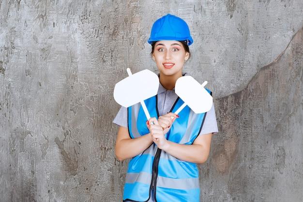 Engenheira de uniforme azul e capacete segurando duas placas de informações em branco com as duas mãos