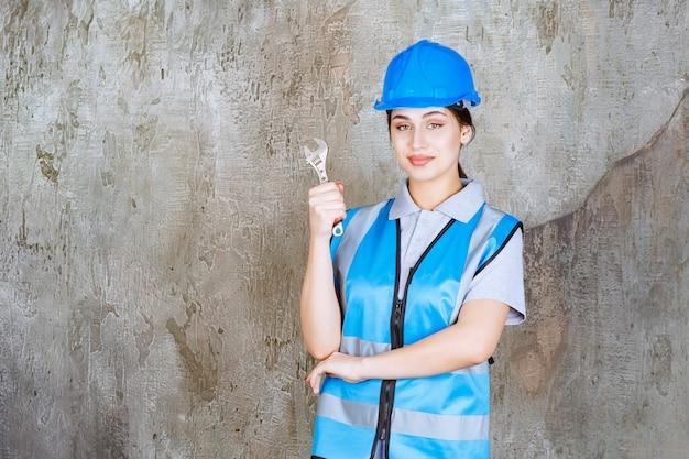 Engenheira de uniforme azul e capacete segurando uma chave metálica.