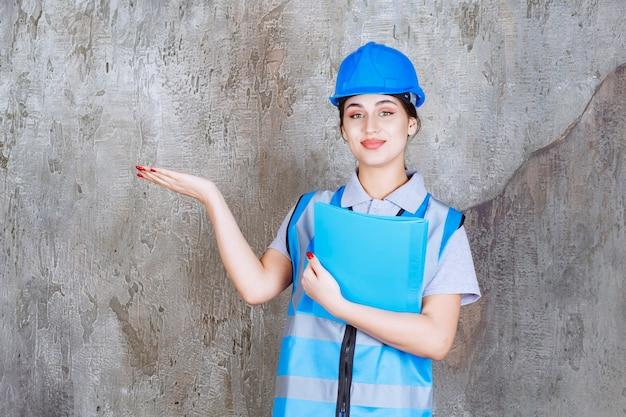 Engenheira de uniforme azul e capacete segurando uma pasta de relatório azul e apontando para alguém ao redor.