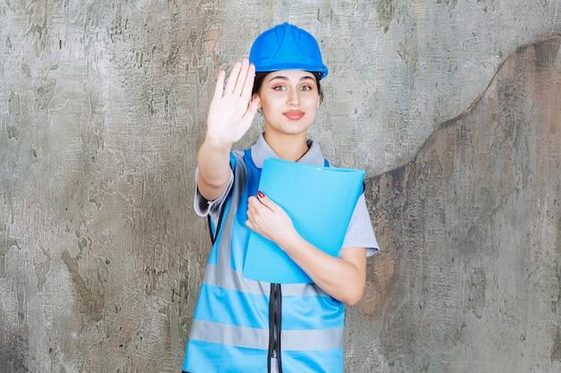 Engenheira de uniforme azul e capacete segurando uma pasta de relatório azul e parando alguém
