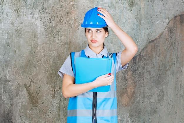 Engenheira de uniforme azul e capacete segurando uma pasta de relatório azul e parece apavorada e assustada.