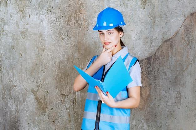 Engenheira de uniforme azul e capacete segurando uma pasta de relatório azul e parece pensativa.