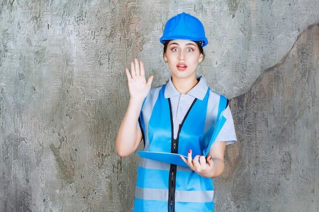 Engenheira de uniforme azul e capacete segurando uma pasta de relatório azul, lendo e fazendo perguntas.