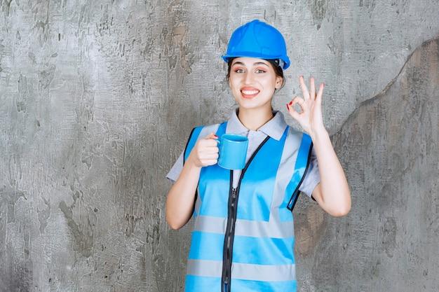 Engenheira de uniforme azul e capacete segurando uma xícara de chá azul e mostrando sinal de prazer.