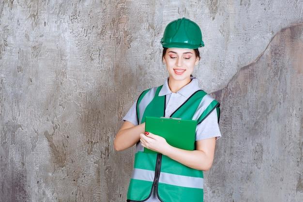 Engenheira de uniforme verde e capacete segurando a pasta do projeto.
