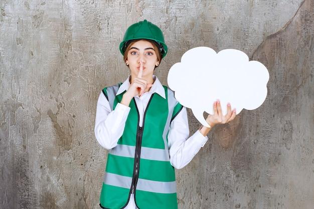 Engenheira de uniforme verde e capacete segurando um quadro de informações em forma de nuvem e pedindo silêncio