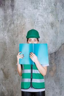 Engenheira de uniforme verde e capacete segurando uma pasta de projeto azul e escondendo o rosto atrás dela.