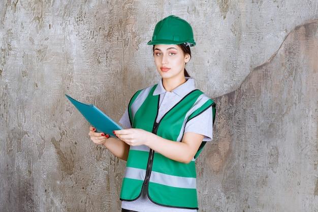 Engenheira de uniforme verde e capacete segurando uma pasta de projeto azul.
