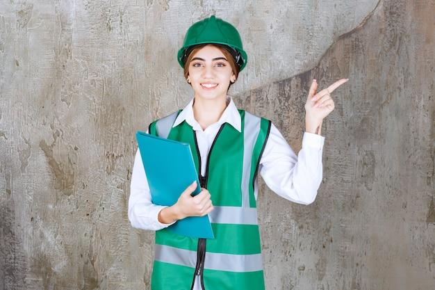 Engenheira de uniforme verde e capacete segurando uma pasta de projeto verde e apontando para o lado direito.